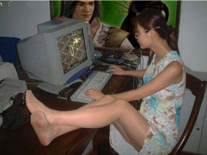 teenage girl skirt legs on the table playing internet gaming computer in Vietnam Cu Lao Tien Giang Go Cong Tan Thoi Tan Phu Dong